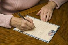 Mulher sênior que escreve uma letra com pena e papel Fotos de Stock Royalty Free
