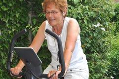 Mulher sênior que escuta a música durante o exercício Fotografia de Stock Royalty Free