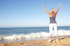 Mulher sênior que estica na praia foto de stock