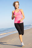 Mulher sênior que exercita na praia Fotos de Stock Royalty Free