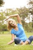 Mulher sênior que exercita no parque Imagens de Stock