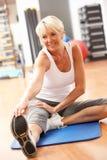 Mulher sênior que faz esticando exercícios Fotografia de Stock