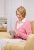 Mulher sênior que faz malha no sofá em casa Fotografia de Stock