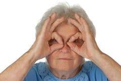 Mulher sênior que olha com binocular imaginário imagens de stock royalty free