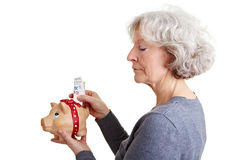 Mulher sênior que põr o dinheiro em piggy Fotos de Stock