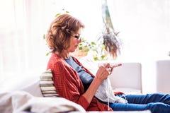 Mulher sênior que relaxa em casa fotos de stock