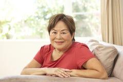 Mulher sênior que relaxa na cadeira em casa Foto de Stock Royalty Free