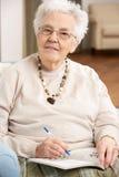 Mulher sênior que relaxa na cadeira em casa Fotografia de Stock Royalty Free