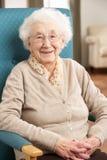 Mulher sênior que relaxa na cadeira em casa Fotografia de Stock