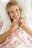 Mulher sênior que relaxa na cama Foto de Stock
