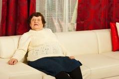 Mulher sênior que relaxa no sofá Imagem de Stock