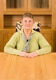 Mulher sênior que senta-se na tabela com copyspace abaixo imagens de stock