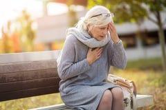 Mulher sênior que sofre de uma dor de cabeça imagens de stock royalty free