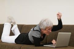 Mulher sênior que trabalha em um portátil imagens de stock royalty free