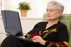 Mulher sênior que usa o computador portátil Fotografia de Stock Royalty Free