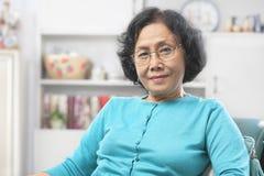 A mulher sênior relaxa em casa imagem de stock royalty free