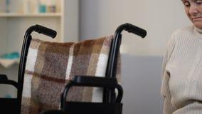 Mulher só infeliz que senta-se na cadeira de rodas no lar de idosos, sentimento saudoso video estoque