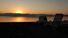 Mulher só irreconhecível na praia vazia que espera o nascer do sol video estoque