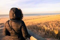 Mulher só no revestimento que olha o mar Imagem de Stock Royalty Free