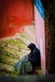 A mulher só pobre do trabalho da senhora idosa senta-se na rua da cidade com o vestido colorido tradicional de musselina, Marroco imagens de stock