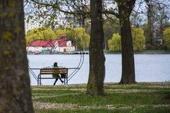 Mulher só que senta-se apenas em um banco em um bloco perto do lago imagem de stock