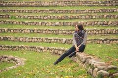 Mulher só que senta-se apenas nas pedras no jardim do outono imagens de stock