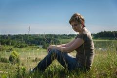 Mulher só que senta-se com ela para trás no campo verde Imagens de Stock