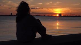 Mulher só que senta-se no cais Sonhando e apreciando o por do sol video estoque