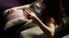 A mulher só triste bebe o álcool na obscuridade Vidro no foco afiado Alcoolismo fêmea filme