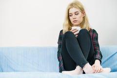 Mulher só triste que senta-se no sofá com caneca imagens de stock