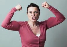 Mulher 40s irritada que dobra seus músculos acima para a metáfora imagens de stock