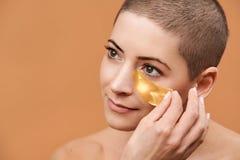 Mulher 30s meados de sorriso que aplica a máscara de olho do colagênio do ouro Foto da mulher caucasiano atrativa com cabeça barb fotografia de stock