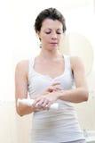 mulher 30s que aplica o creme hidratando Fotos de Stock Royalty Free