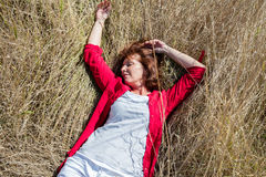 mulher 50s que aprecia o calor do sol que dorme pacificamente na grama seca fotografia de stock