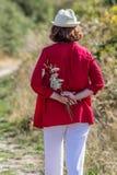 a mulher 50s que dá uma volta ao redor apenas com campo floresce Fotografia de Stock Royalty Free