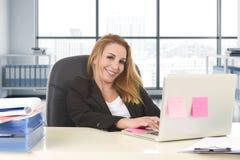 Mulher 40s relaxado com assento seguro de sorriso do cabelo louro na cadeira do escritório que trabalha no laptop imagens de stock