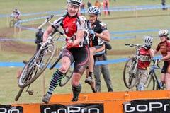 A mulher salta a barreira no evento de Cycloross Fotografia de Stock