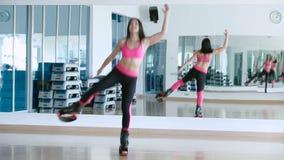 A mulher salta com as sapatas do kangoo no estúdio da dança vídeos de arquivo