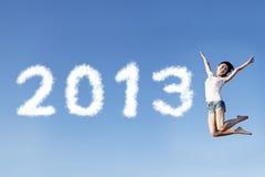 A mulher salta dando boas-vindas ao ano novo 2013 Imagem de Stock