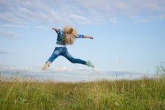 A mulher salta no campo de grama verde Fotografia de Stock