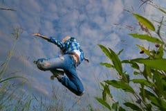 A mulher salta no campo de grama verde Fotos de Stock Royalty Free