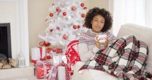 Mulher satisfeita na camiseta que coloca no sofá foto de stock royalty free
