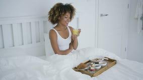 Mulher satisfeita que aprecia o café da manhã na cama vídeos de arquivo