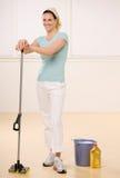 Mulher satisfeita que levanta com o líquido de limpeza do espanador e do assoalho Fotografia de Stock Royalty Free