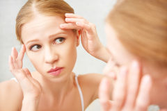 A mulher saudável bonita amedrontou a serra na acne do espelho e no w Imagens de Stock Royalty Free