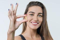 Mulher saudável bonita de sorriso nova no sportswear com vitamina D, E, cápsulas do óleo de peixes omega-3 de A, no fundo branco imagem de stock royalty free