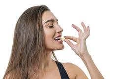 Mulher saudável bonita de sorriso nova no sportswear com vitamina D, E, cápsulas do óleo de peixes omega-3 de A, no fundo isolado imagens de stock