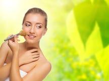 Mulher saudável com a escova da composição no fundo da mola Imagem de Stock Royalty Free