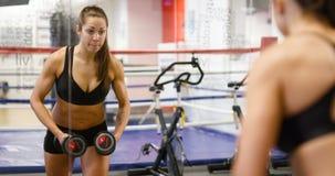 A mulher saudável e bem treinada levanta peso no gym da aptidão video estoque