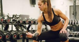 A mulher saudável e bem treinada levanta peso no gym da aptidão vídeos de arquivo